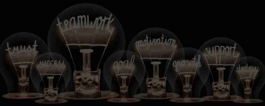 Photo of light bulbs group with shining fibers in a shape of TEAMWORK concept related words isolated on black background