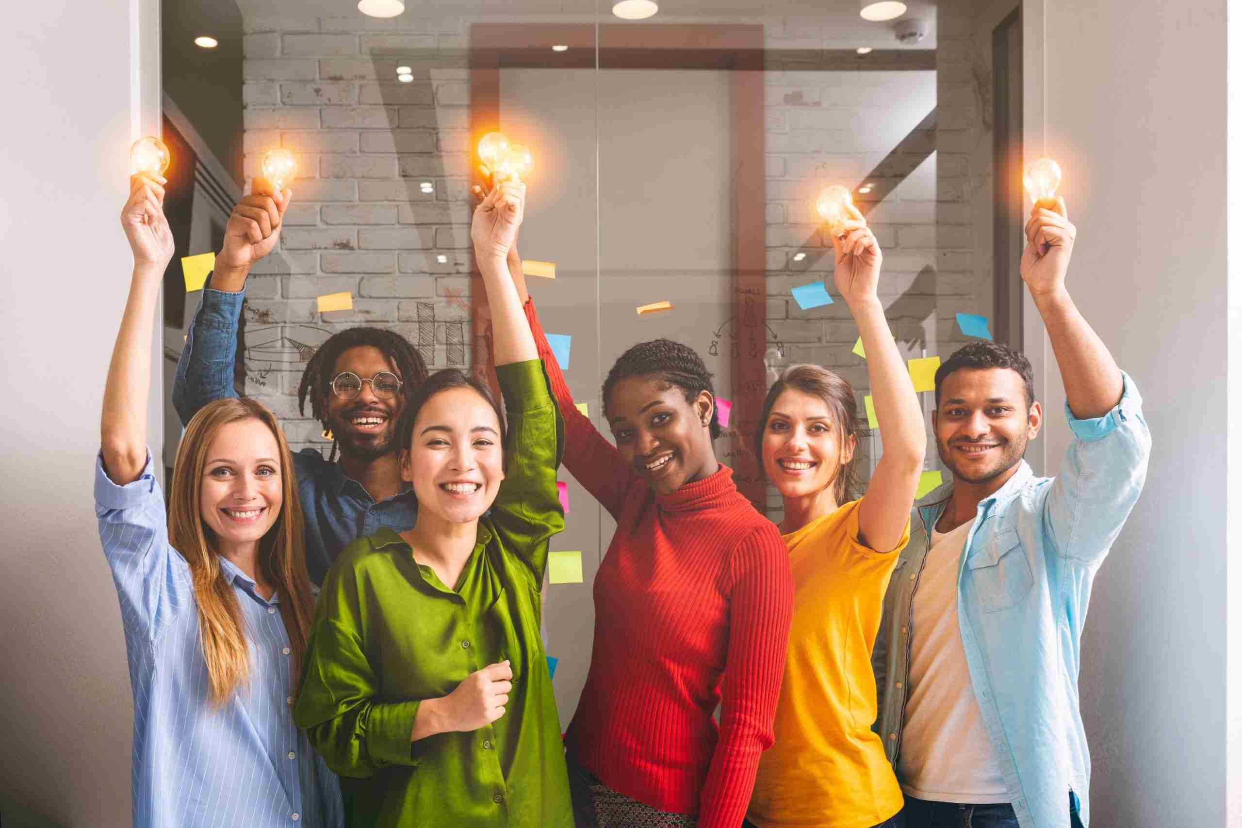 A picture of a team of people holding up lightbulbs, emphasising how a good innovation strategy will place the customer at the centre of the organisation.