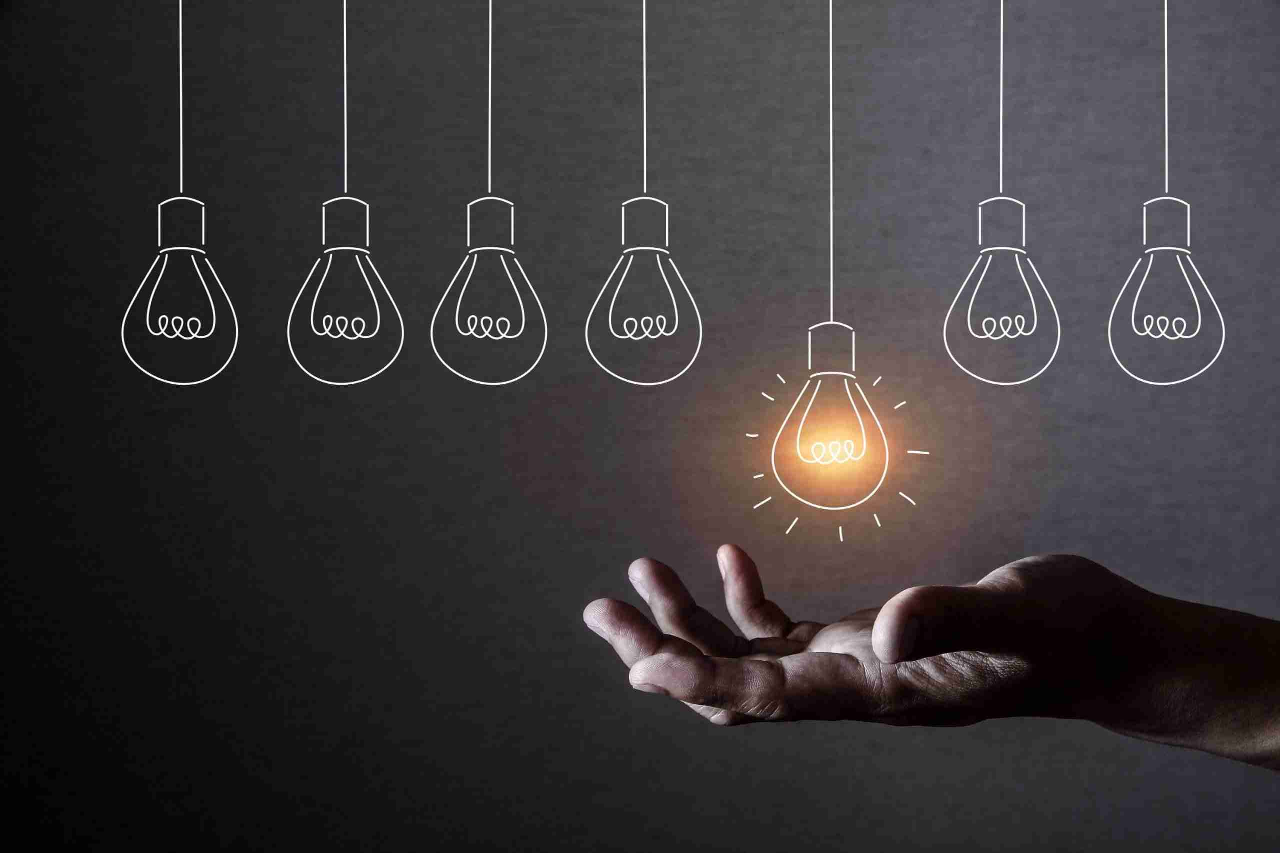 A picture of a set of hanging lightbulbs, with a hand situated underneath to grab them. This signifies the importance of capturing the insights and ideas of staff and customers in crafting an effective innovation strategy.