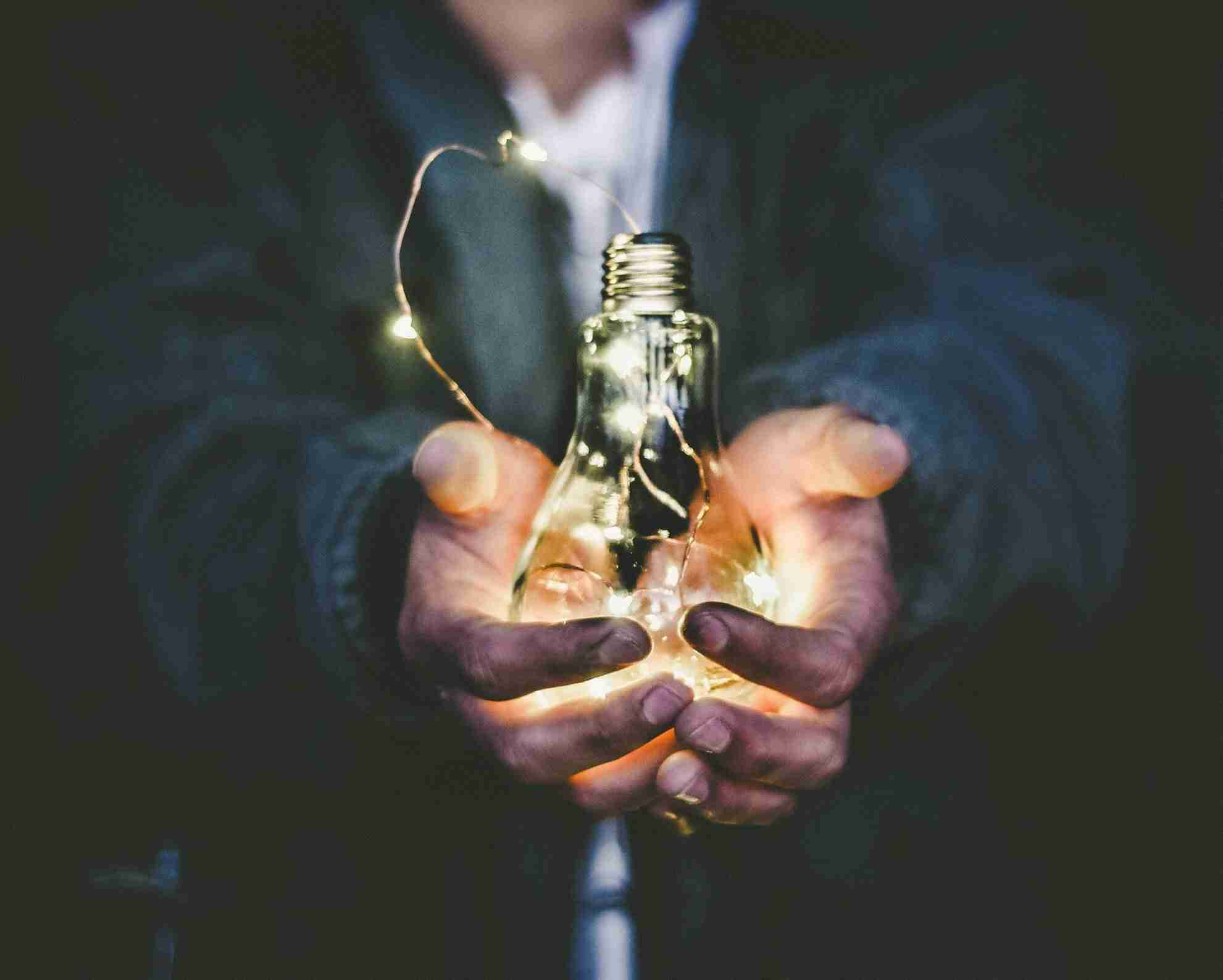 A picture of a single person cradling a lightbulb, demonstrating how a culture of innovation is critical to an effective innovation strategy, and cannot be forced upon a single person, but rather furthered by innovation champions