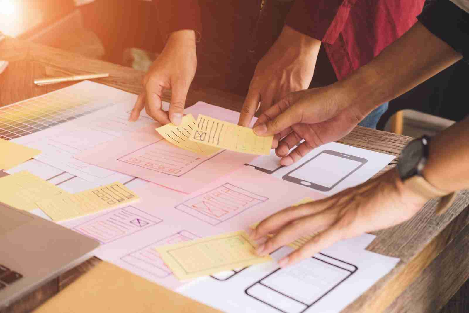 A team of people gathered around a desk doing in-depth customer research as a customer experience consultant