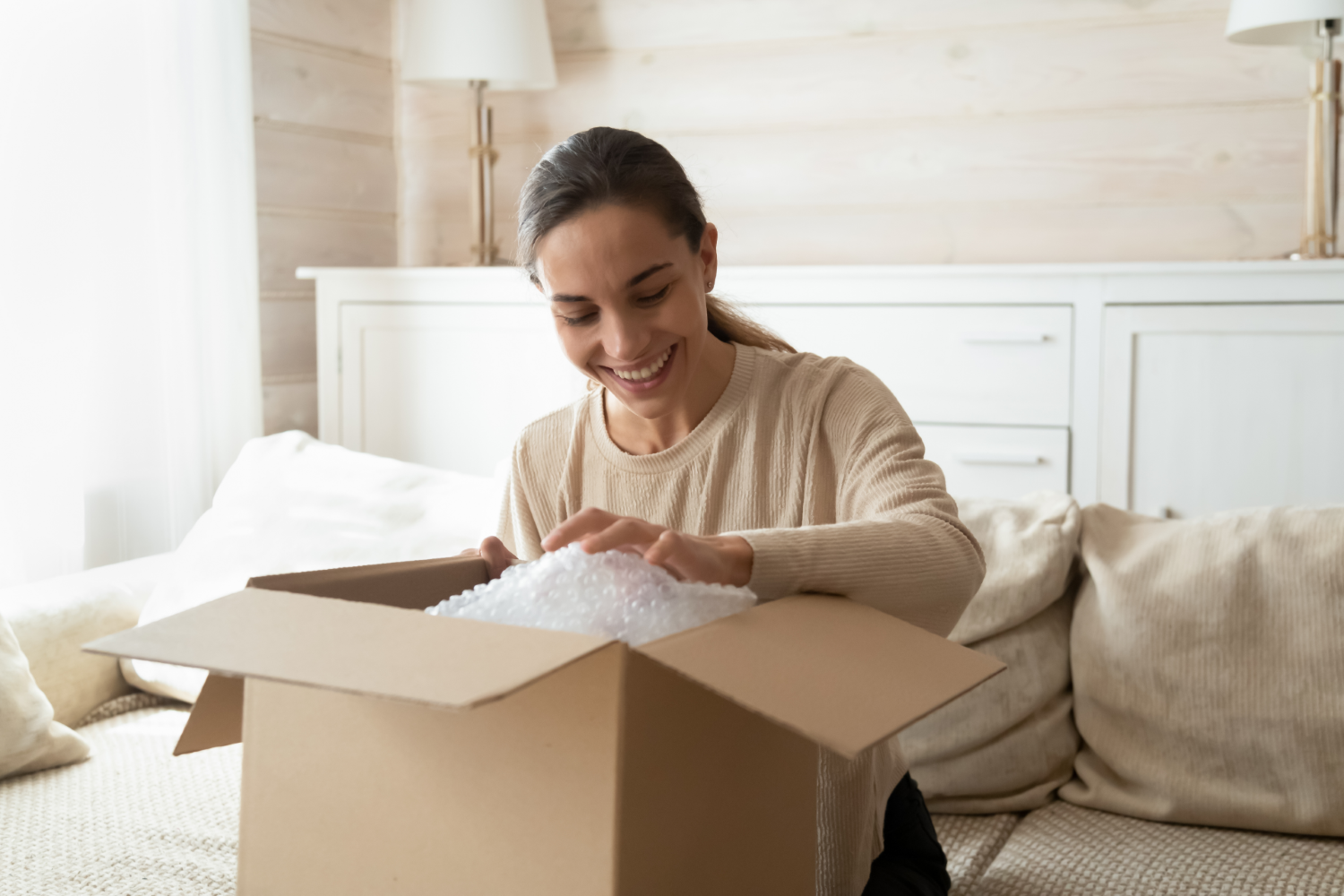 A picture of a joyful person opening a box, representing the potential of a customer value proposition design to allow you to delight your customers.